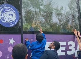 Emirati astronaut waves goodbye to his kids, on bus to launch site