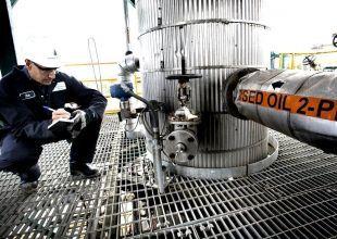 Oil falls $1 as dollar gains, investors shun risk