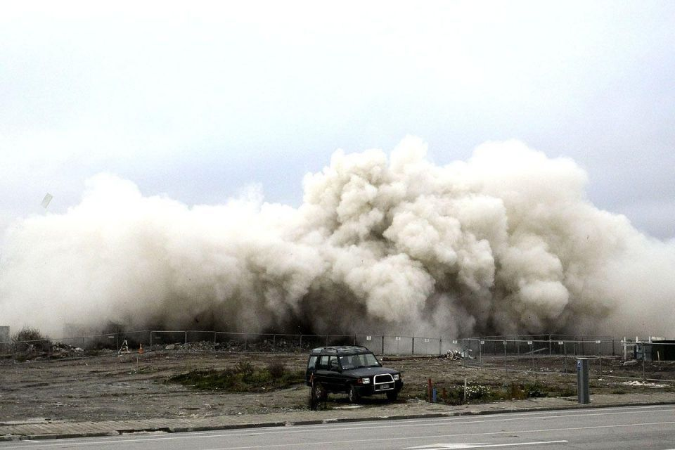 Earthquake damaged building blown up in controlled demolition